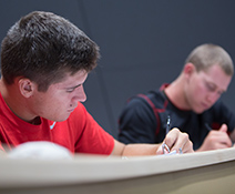 Two male students writing notes during class