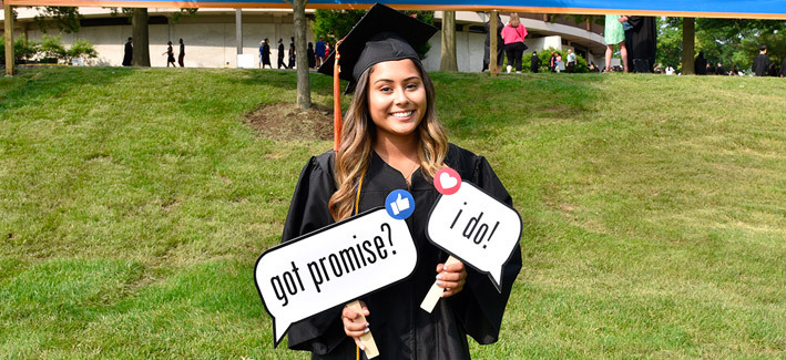 photo of a 2019 ccbc graduate holding a college promise sign