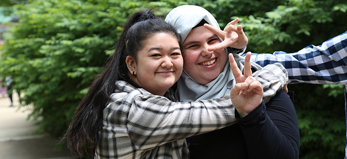 two happy female students hugging