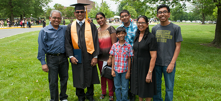 family proudly posing for a picture with their graduate