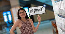 photo of a college promise student holding a promise sign