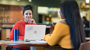 female student sitting at a table with another woman working on her laptop