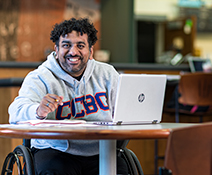 Male CCBC student using his laptop in a cafe smiles for a photo
