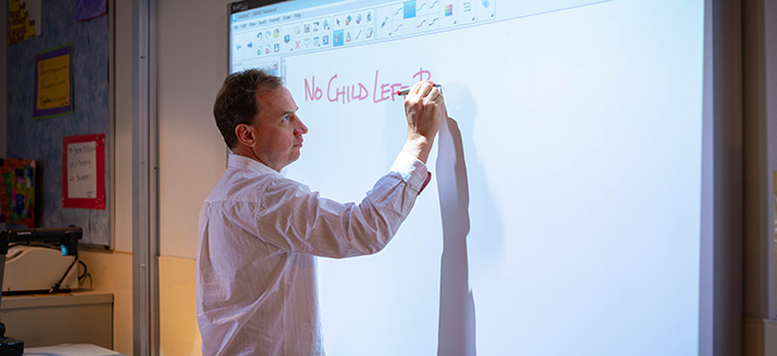 professor writing on a white board in front of class
