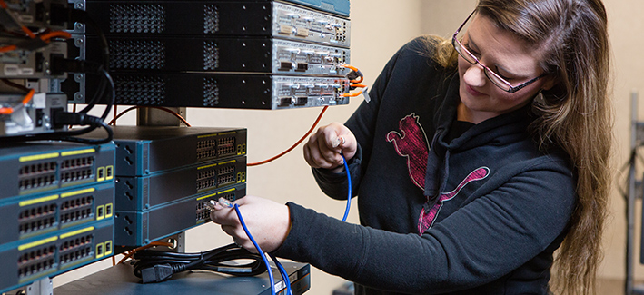 female student plugging a cable into a computer server