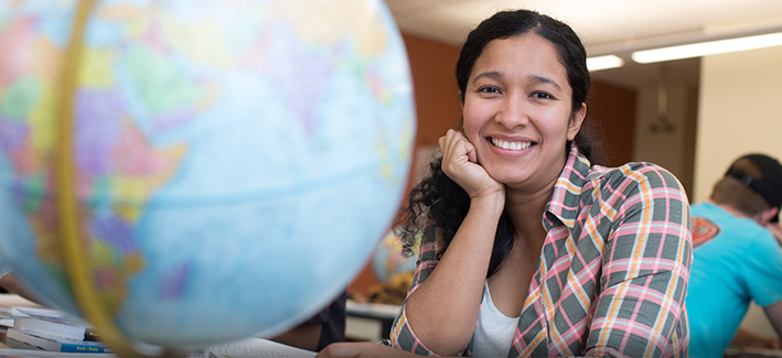 photo of a female student sitting in a classroom with a globe