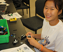 A young students is enjoying learning with Lego's at the CCBC Summer Adventures Learning Camp.