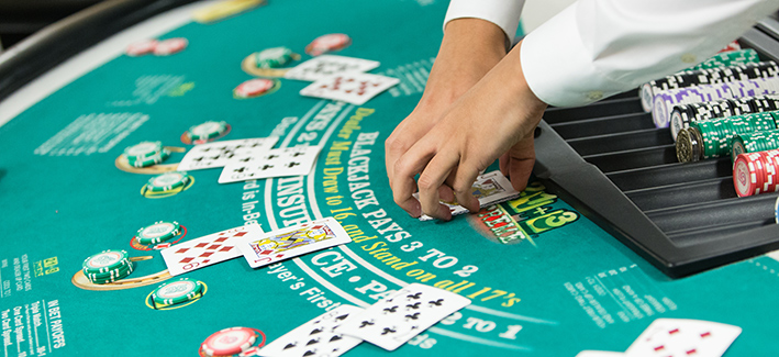 casino dealer dealing cards on table