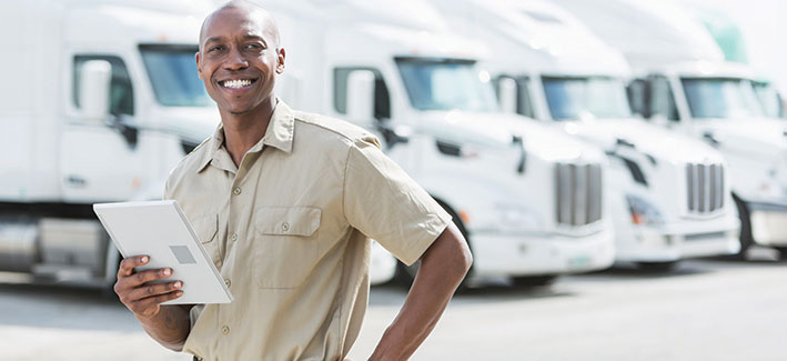 Man standing with clipboard in front of diesel trucks