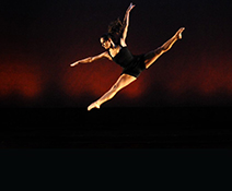 Image of a female dancer leaping across the stage