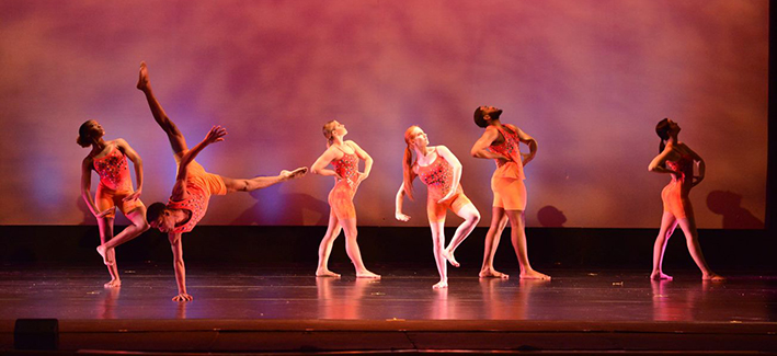 Group of dancers perform on stage