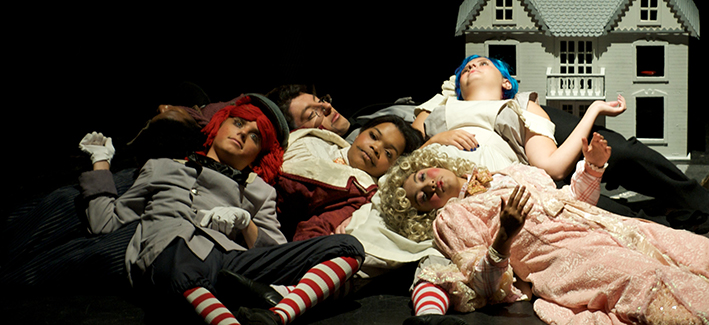 5 women dressed as dolls lay on one another on stage