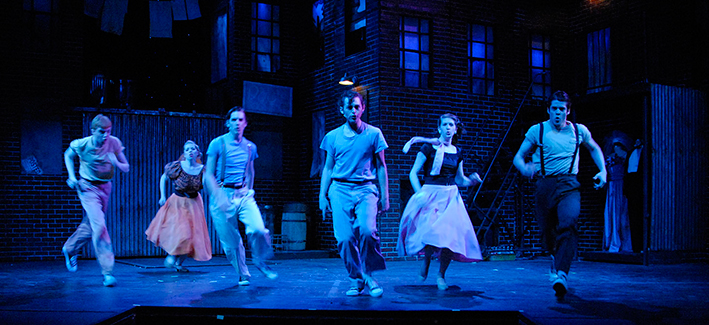 6 actors dance on stage in a straight line in a blue light.