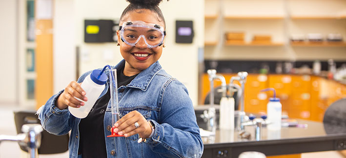 female chemistry student wearing protective glasses holding a flask