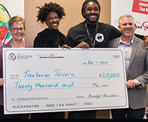 winner of the business plan competition holding a large check