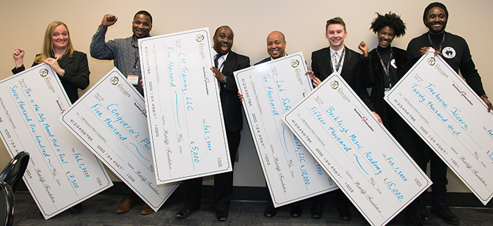 Winners of the Business Plan Competition holding large checks