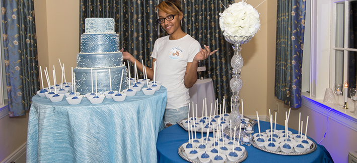 Young women stands behind a cake that she has made at an event