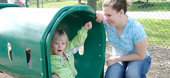 Little girl outside on a slide with a teacher