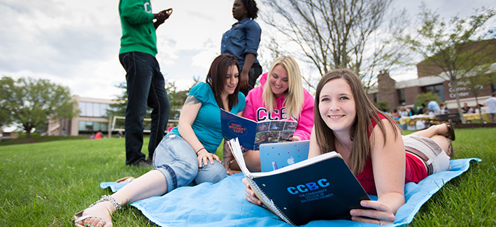 Students lounging and reading on the lawn.