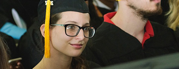 female student in her cap and gown on graduation day