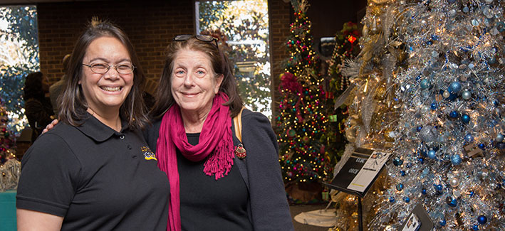 Two CCBC staff members stand in front of Christmas trees