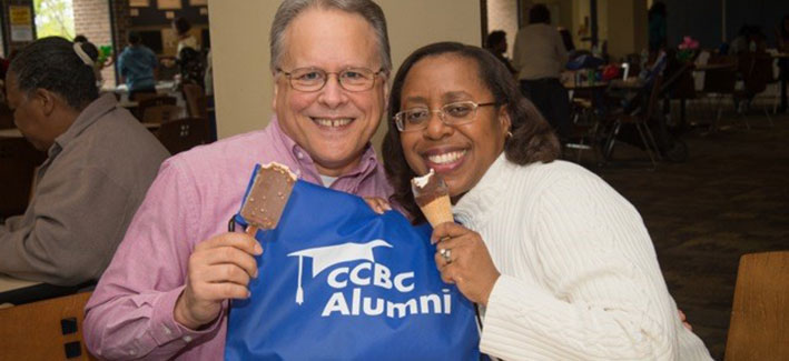Two CCBC Alumni hold up a CCBC Alumni bag