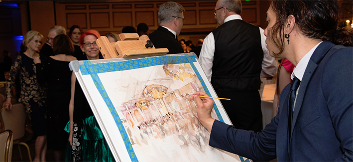 photo of an artist drawing a picture on canvas at the CCBC gala