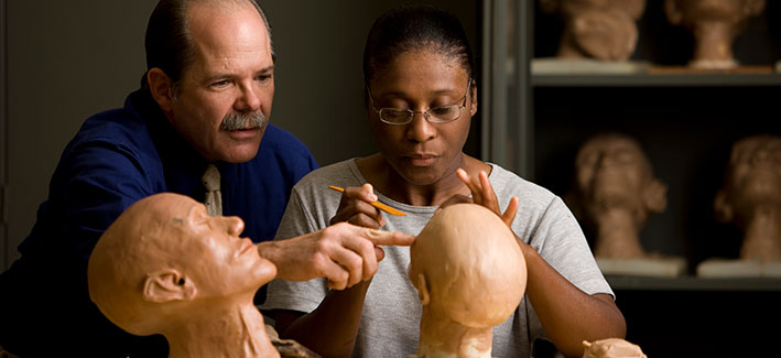 professor helping a student working on facial reconstruction in the mortuary science program