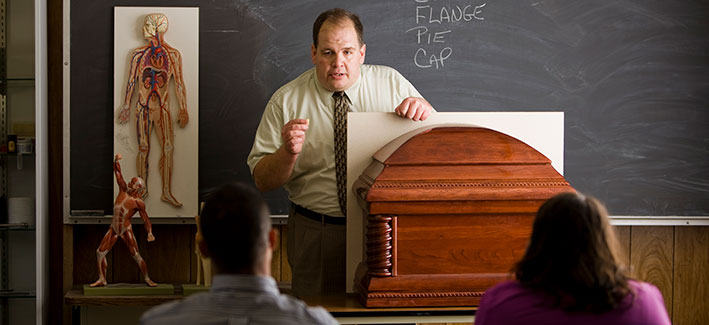 professor giving a lecture in a mortuary science class