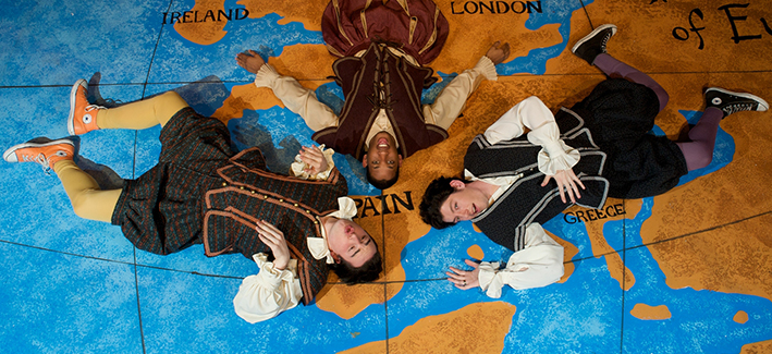 three actors sprawled across a map of Europe with comedic expressions