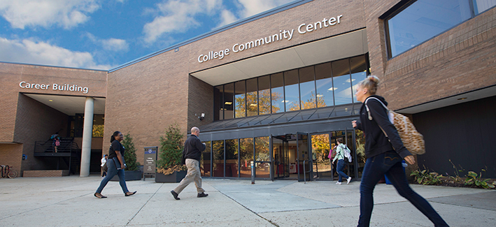 Picture of the College Community Building with students entering and exiting the building