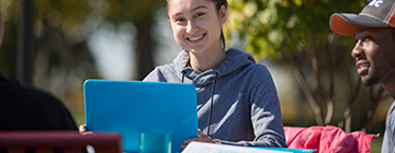 CCBC female student sits in front of her laptop outside on a sunny day