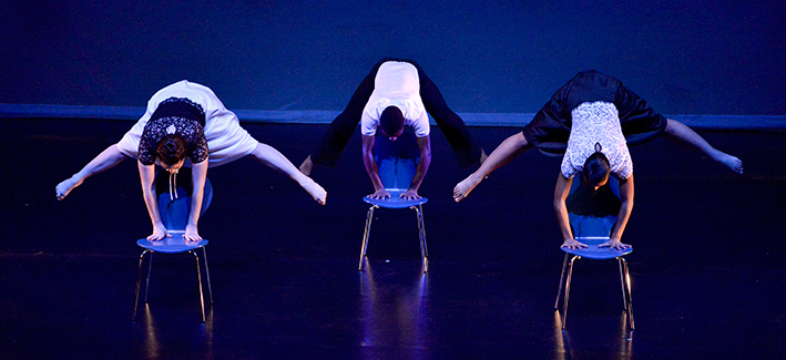 students doing hand stands on chairs for a dance performance