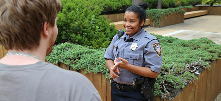 photo of a female public safety officer talking with a student