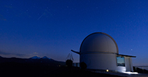 Photo of a large dome telescope with dark blue sky with stars in the background