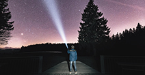 person shines a flash light into the night sky