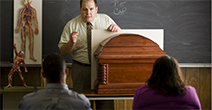 Mortuary Science instructor standing next to a casket speaks to a classroom of students