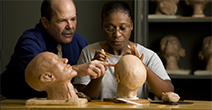 Male instructor and female student work together sculpting a clay head