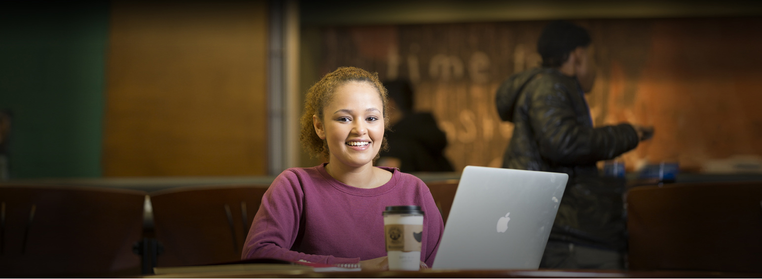 A young CCBC student sits in front of her laptop