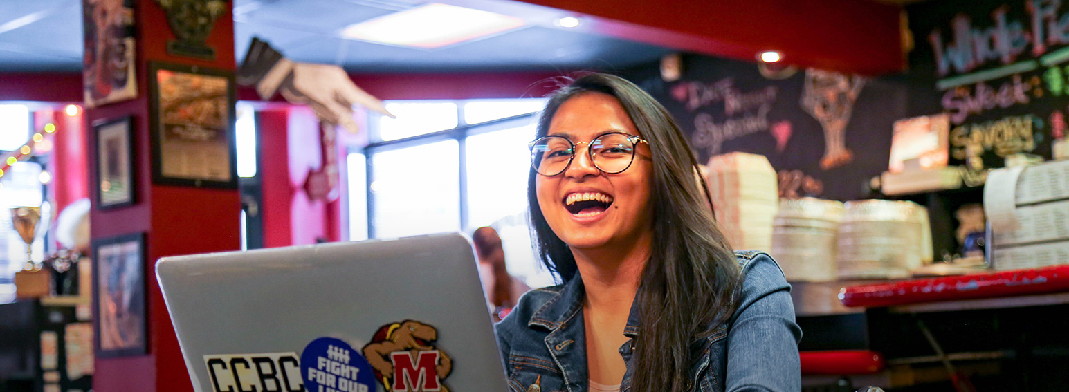 Photo of a ccbc student smiling while working on her laptop