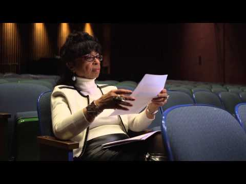 senior woman sitting in a theater reading a script